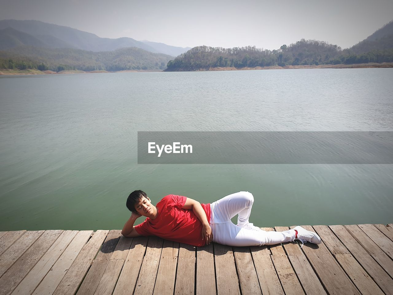 High angle view of man relaxing on pier by lake