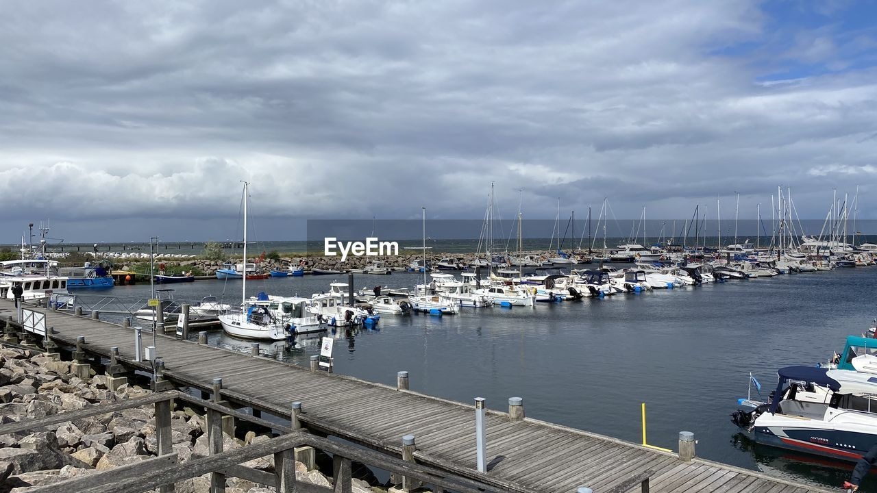 SAILBOATS MOORED IN HARBOR AGAINST SKY