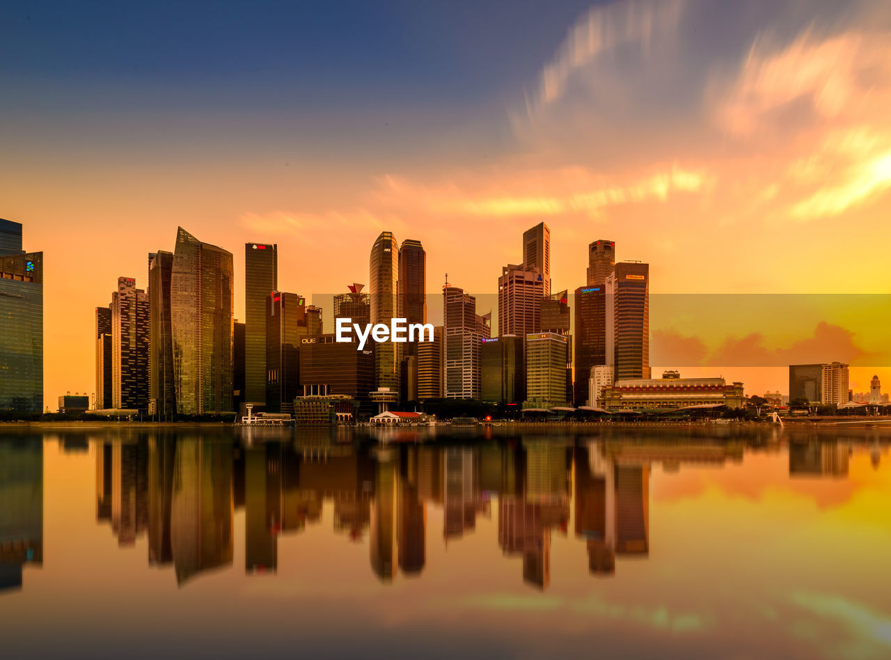 Reflection Of Modern Buildings On Marina Bay During Sunset