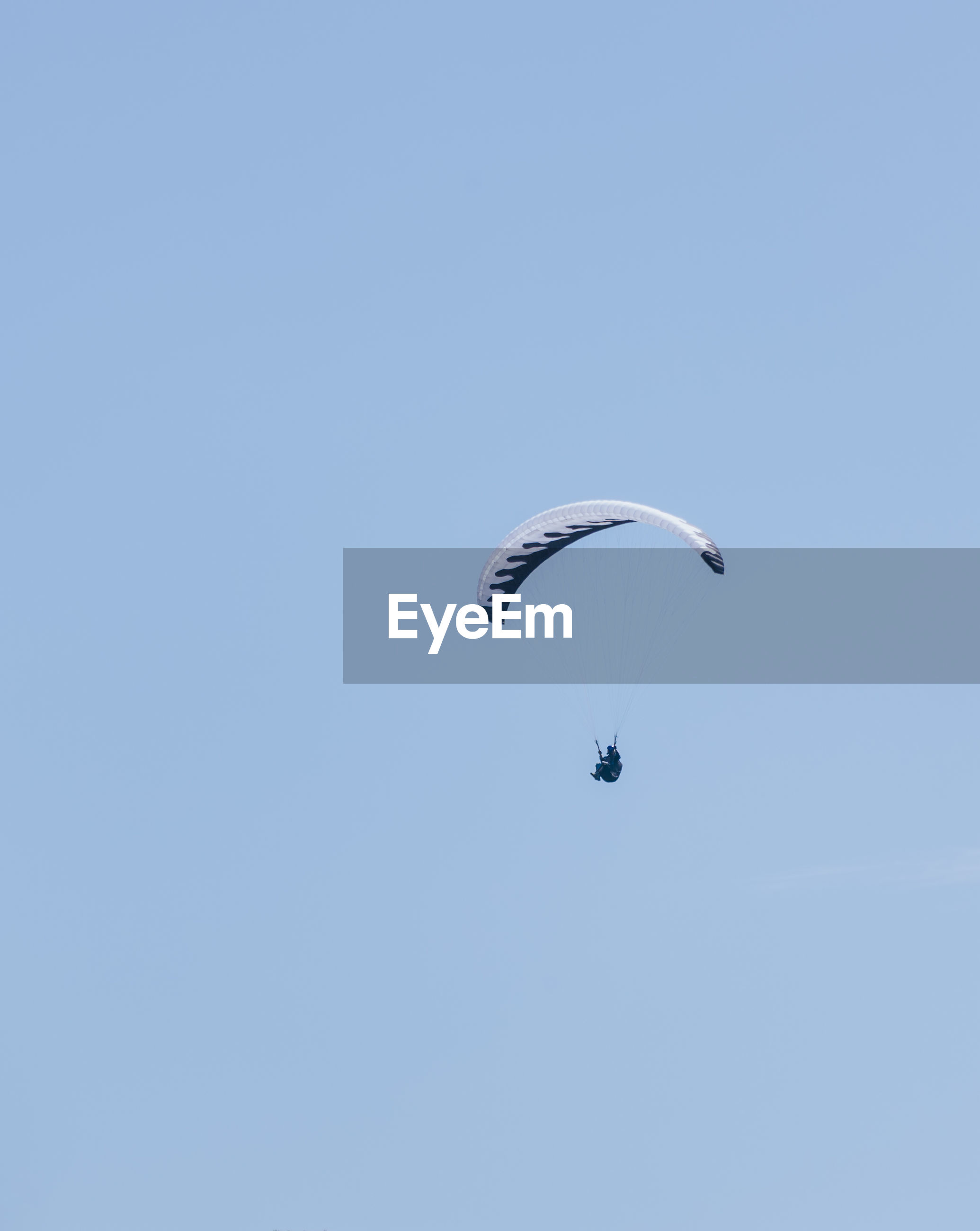 Low angle view of person paragliding in clear blue sky