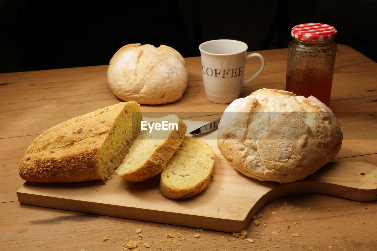 food and drink, bread, food, table, freshness, still life, indoors, drink, cup, wellbeing, wood - material, no people, refreshment, cutting board, healthy eating, mug, baked, ready-to-eat, close-up, breakfast, meal, tea cup, tray