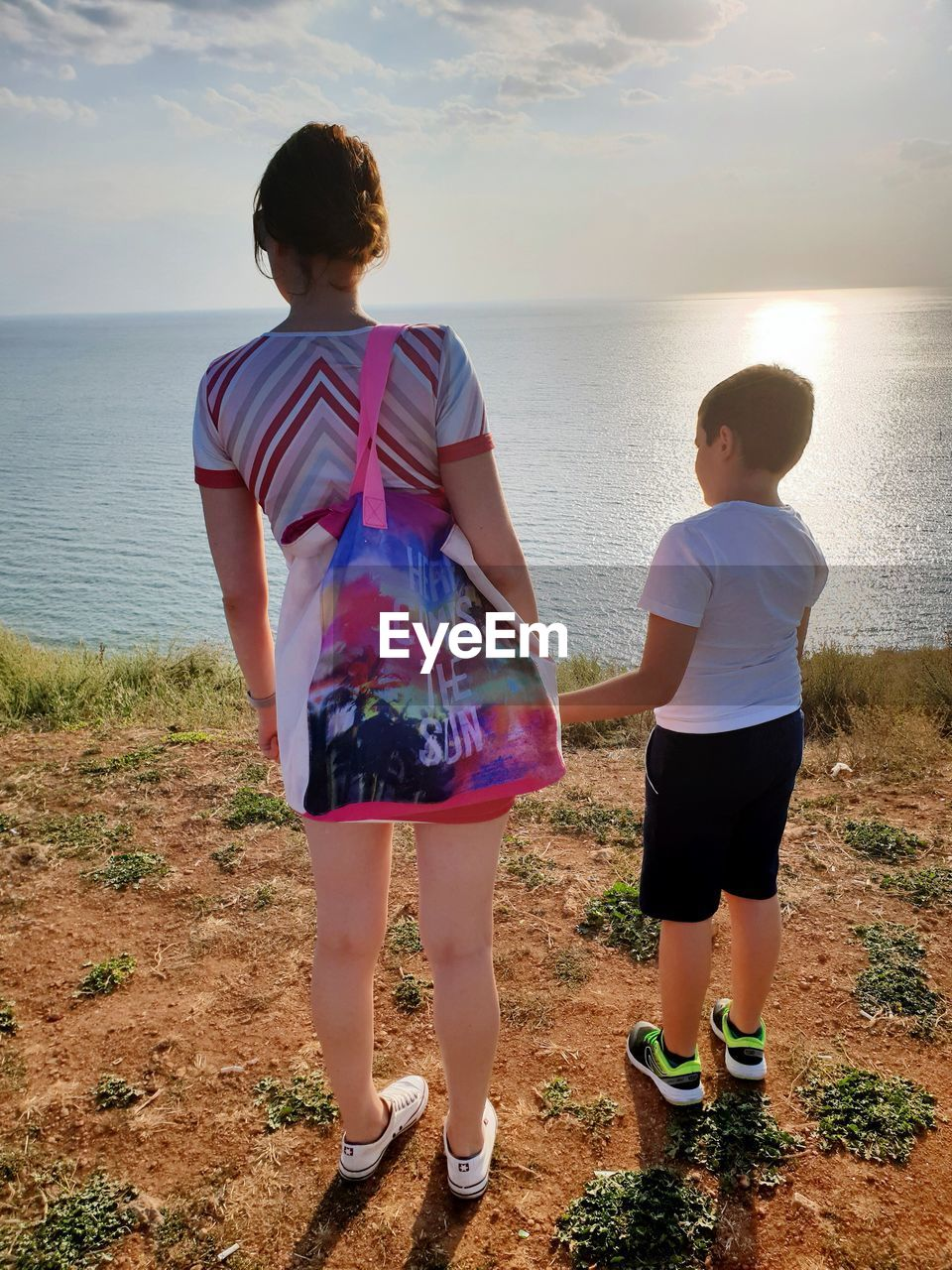 childhood, two people, child, water, togetherness, real people, boys, family, leisure activity, full length, males, sky, men, bonding, casual clothing, sea, nature, rear view, positive emotion, sister, outdoors, horizon over water