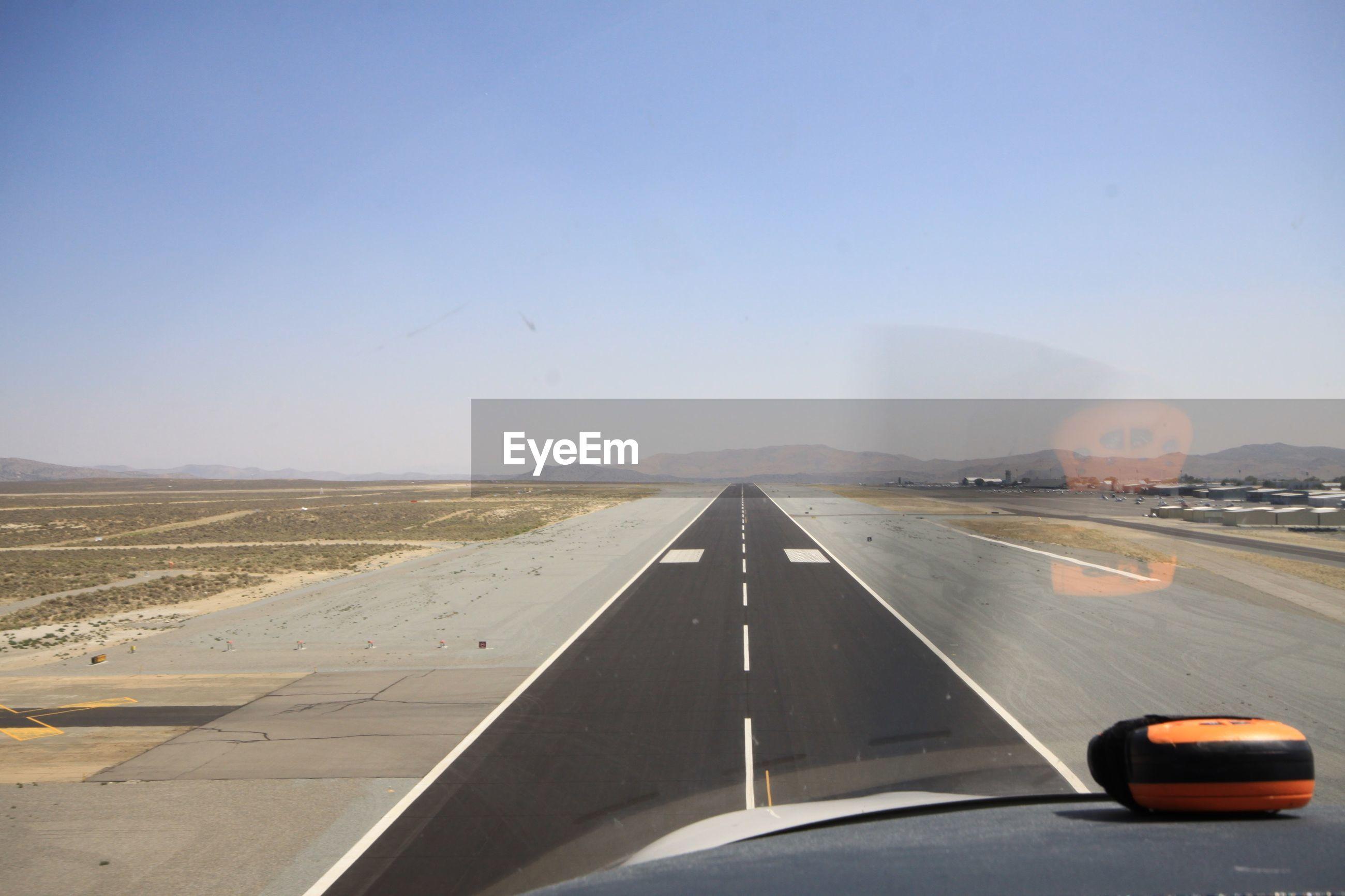 Runway seen through airplane windshield against clear blue sky