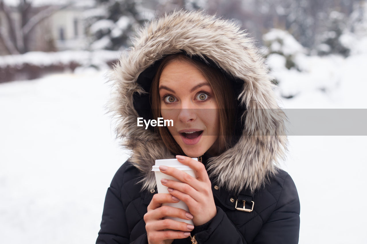 Portrait of surprised woman wearing warm clothing in winter