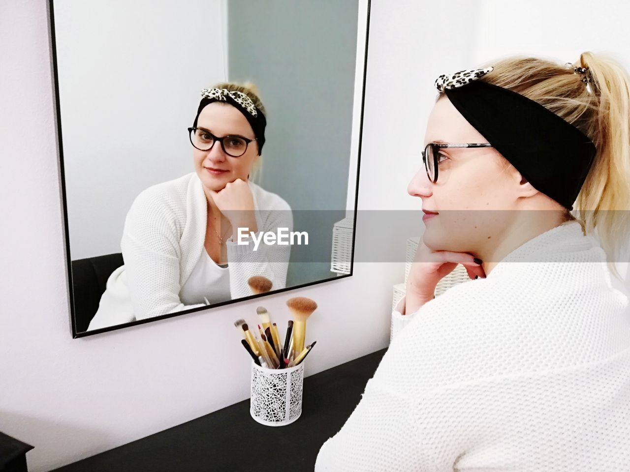 Portrait of young woman with her reflection in mirror