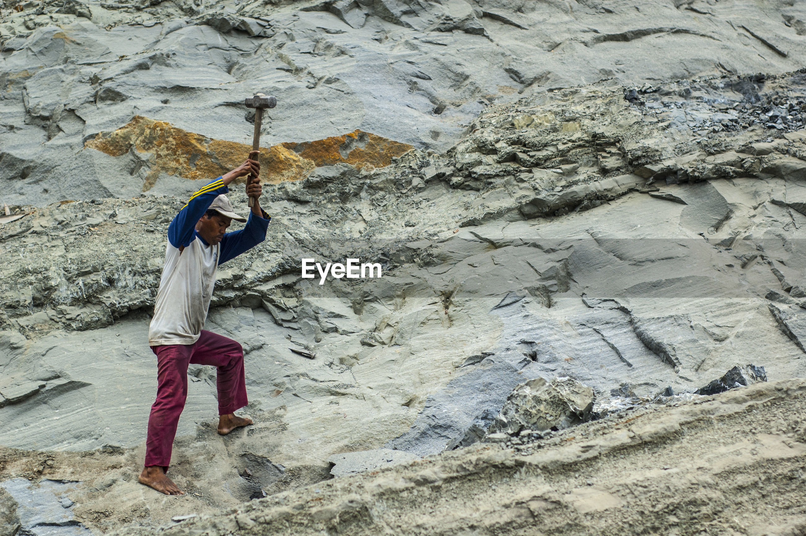 Side view of man hammering rock formations