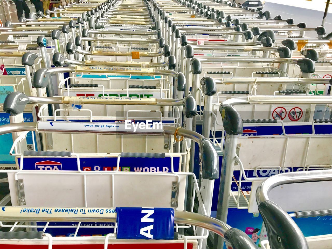 in a row, shopping cart, order, no people, indoors, industry, factory, metal, large group of objects, machinery, repetition, technology, abundance, absence, seat, blue, supermarket, conveyor belt, luggage cart, man made object, silver colored