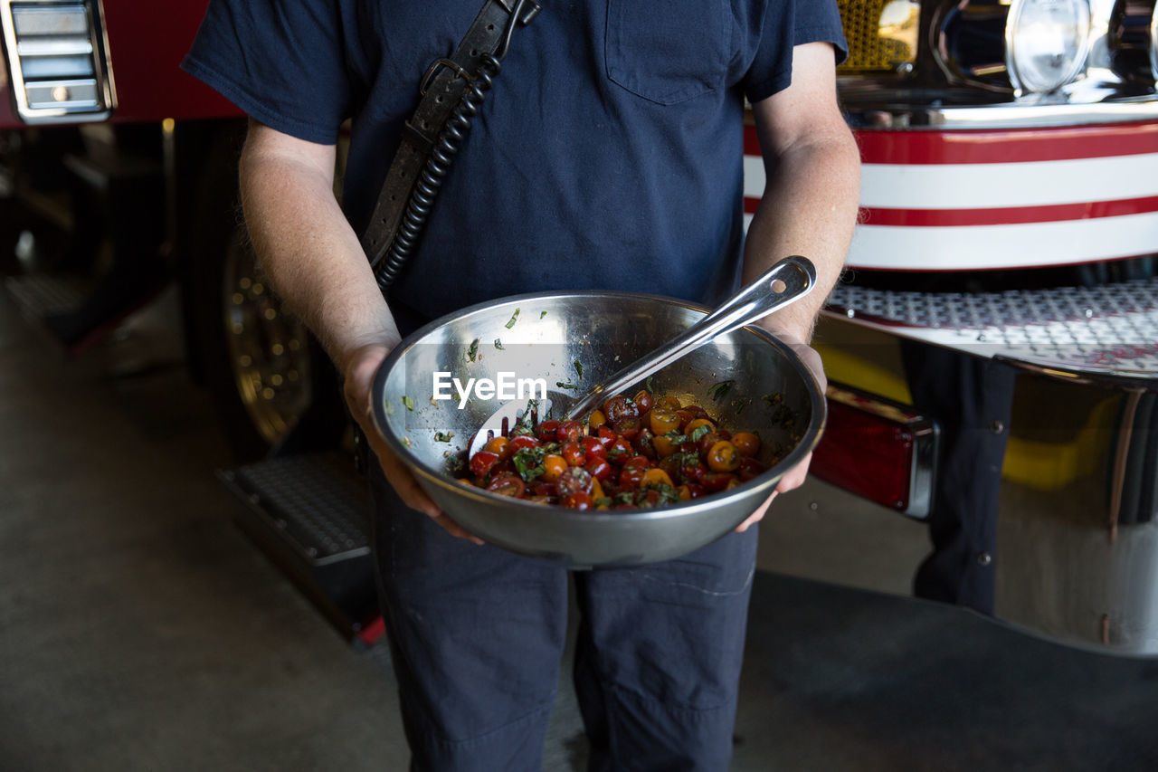 Midsection Of Man Holding Cherry Tomatoes Container