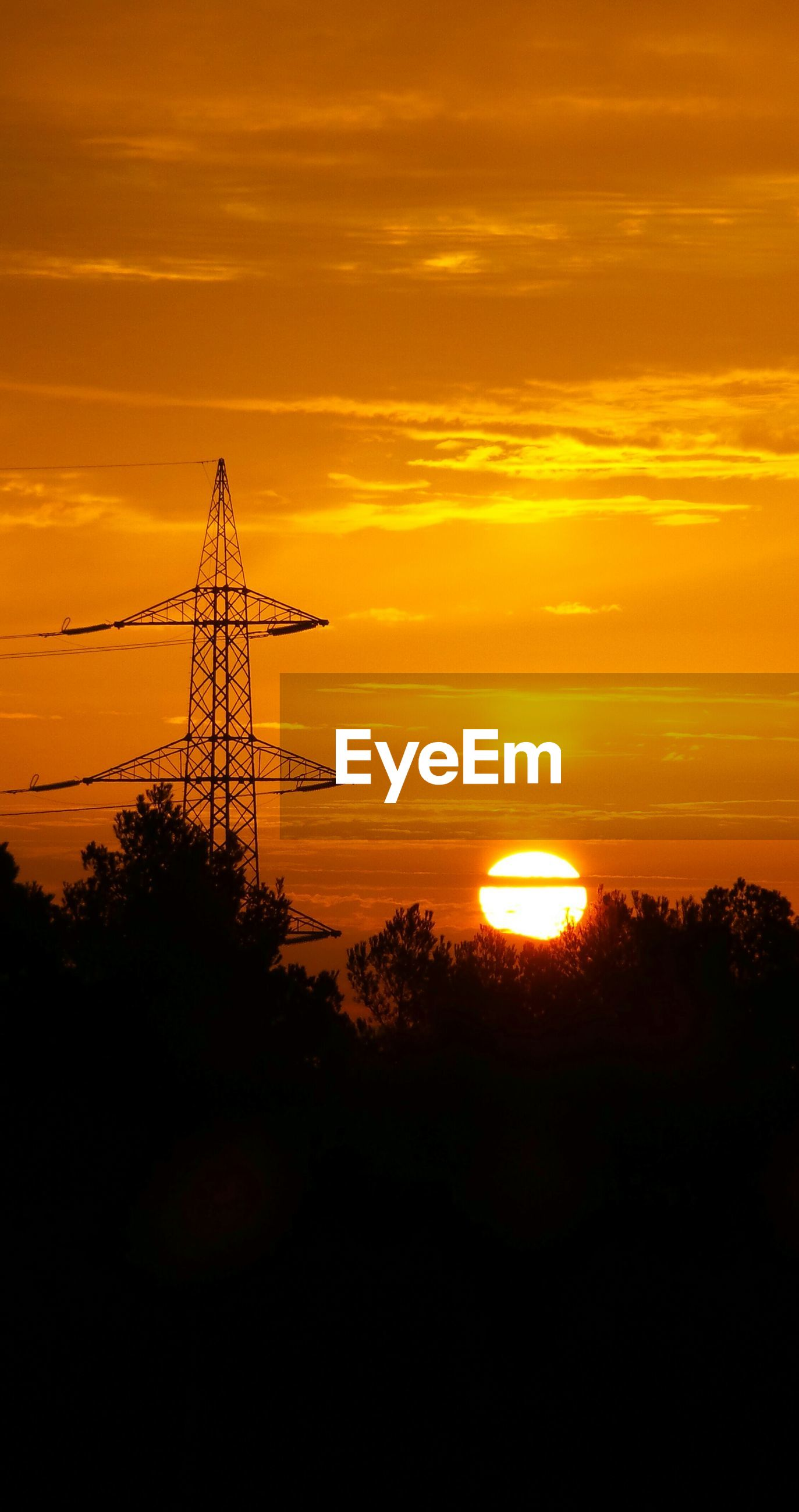 Low angle view of silhouette electricity pylon by trees against orange sky