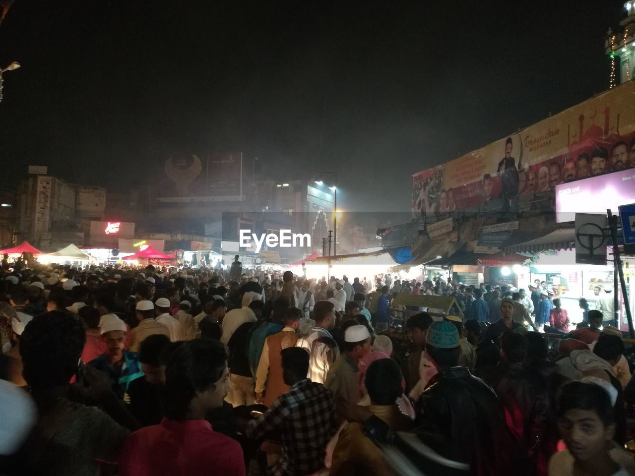 crowd, group of people, real people, large group of people, night, illuminated, women, men, lifestyles, city, architecture, leisure activity, adult, built structure, building exterior, street, city life, lighting equipment, outdoors, nightlife, stage, street market