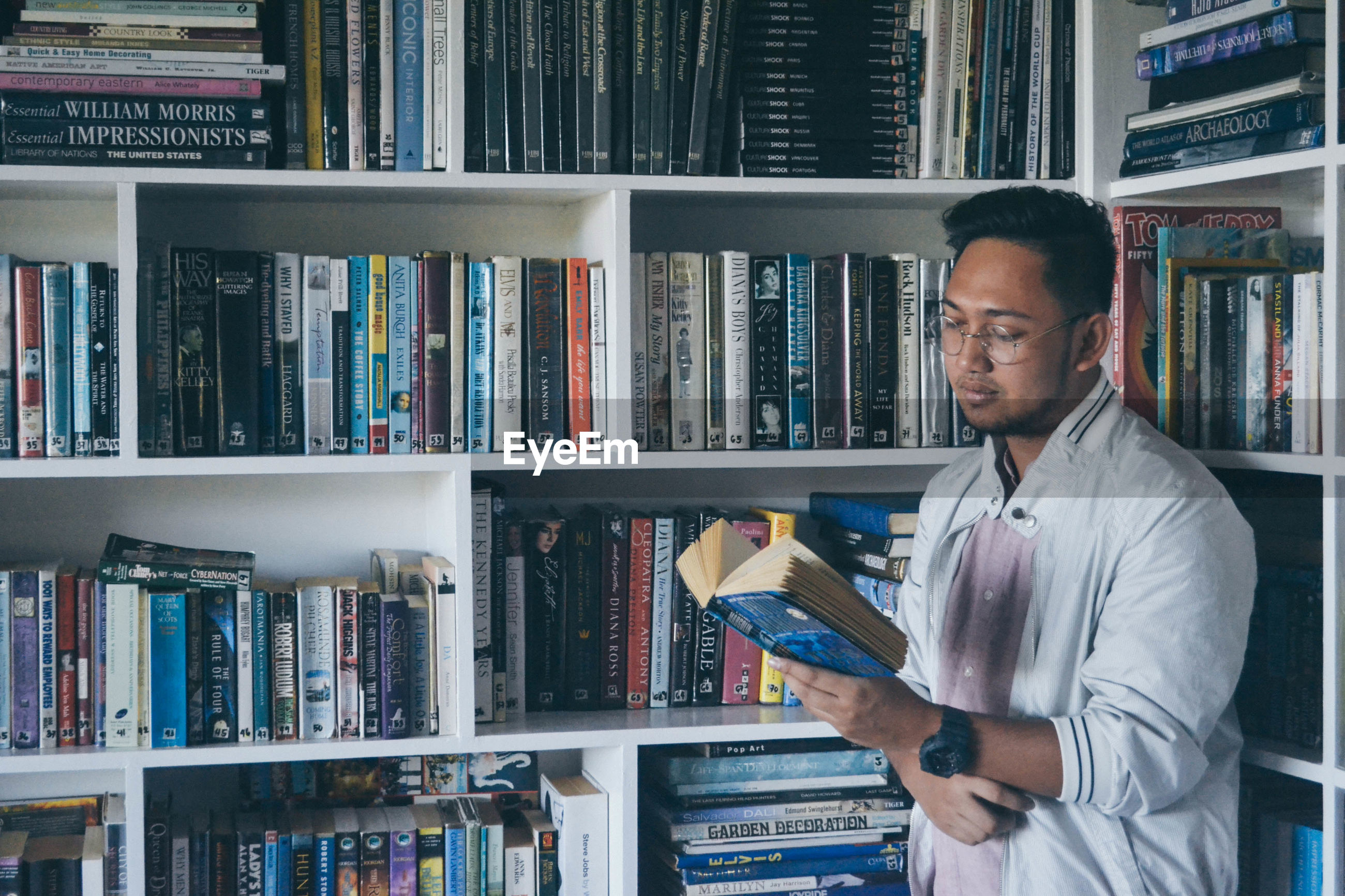 Young man reading book against shelves
