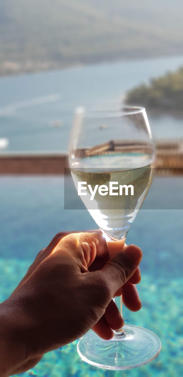 human hand, human body part, refreshment, food and drink, hand, drink, water, holding, glass, focus on foreground, one person, alcohol, lifestyles, real people, day, household equipment, nature, close-up, freshness, body part, outdoors, finger, swimming pool