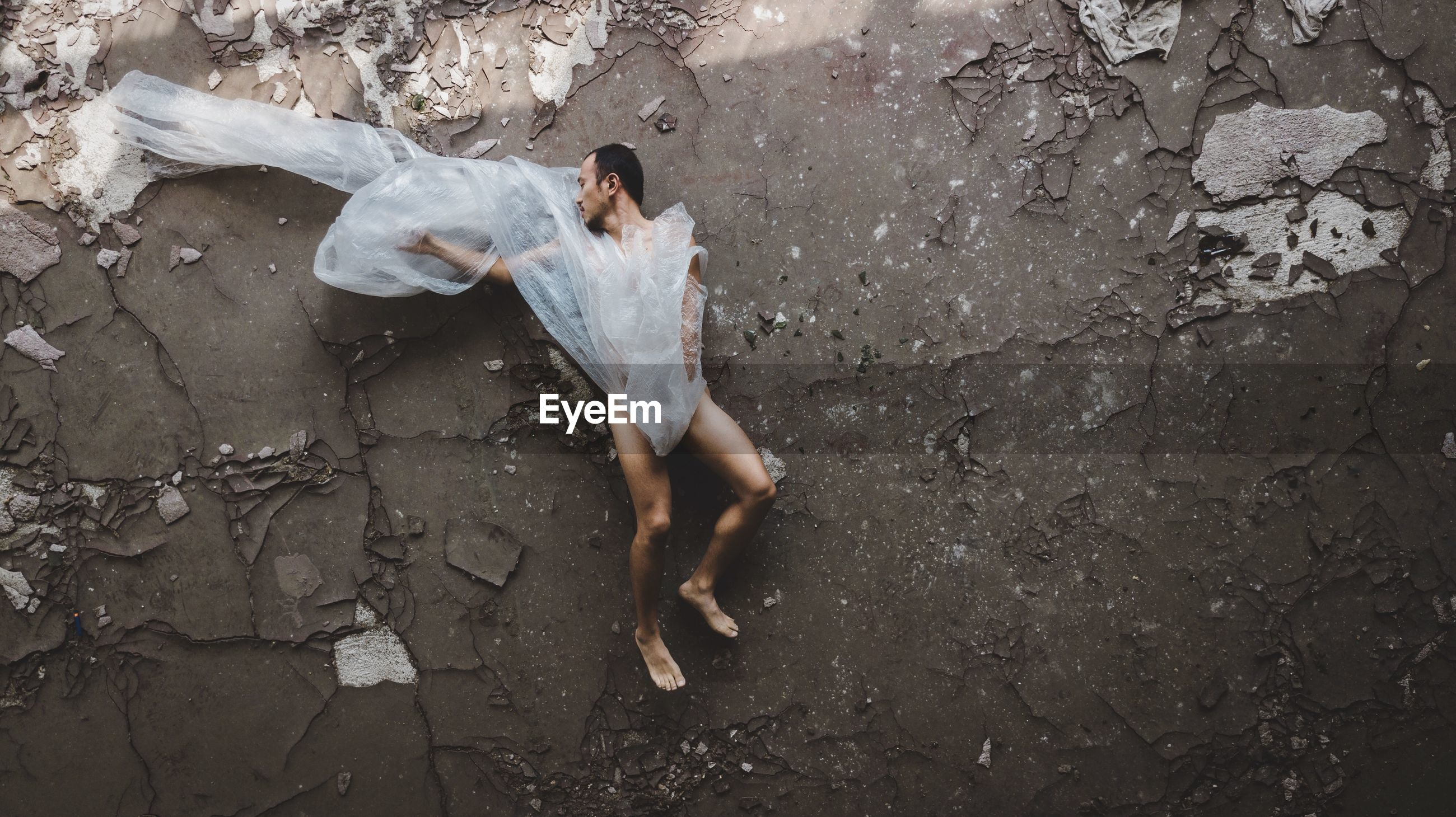 High angle view of naked man wrapped in plastic lying on abandoned floor