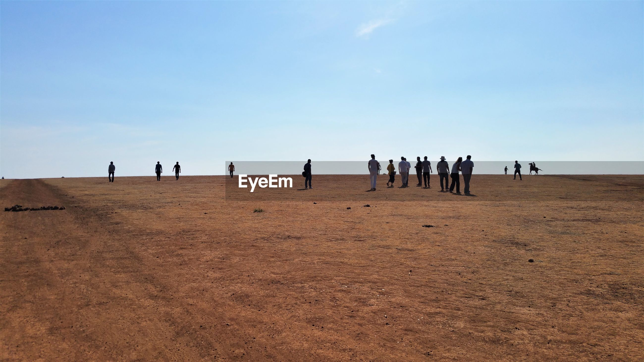 People standing on sand at desert against sky during sunny day
