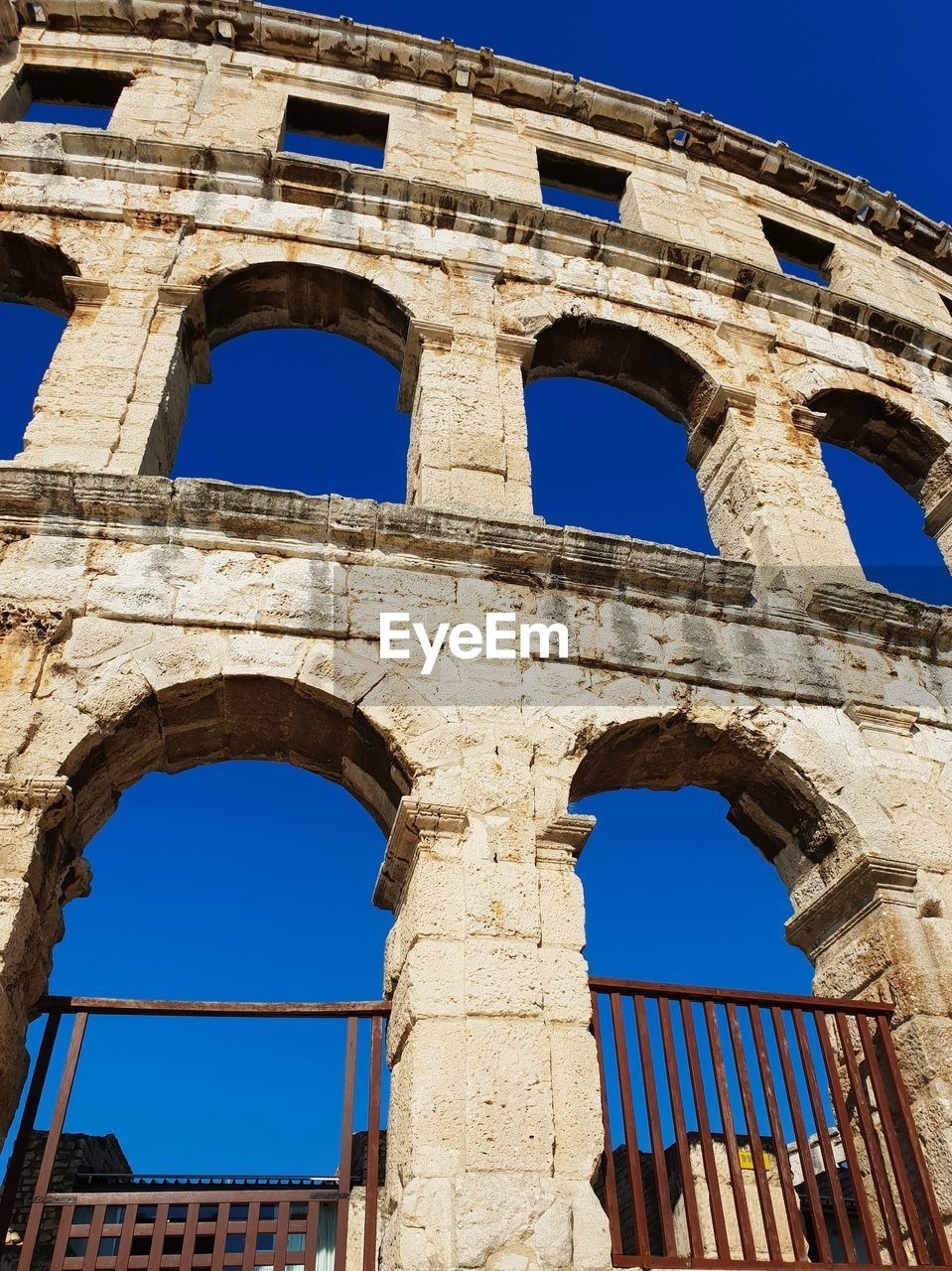 history, architecture, the past, ancient, old ruin, built structure, arch, low angle view, sky, amphitheater, ancient civilization, tourism, clear sky, travel destinations, nature, damaged, building exterior, day, travel, no people, ruined, archaeology, outdoors, architectural column, ancient history