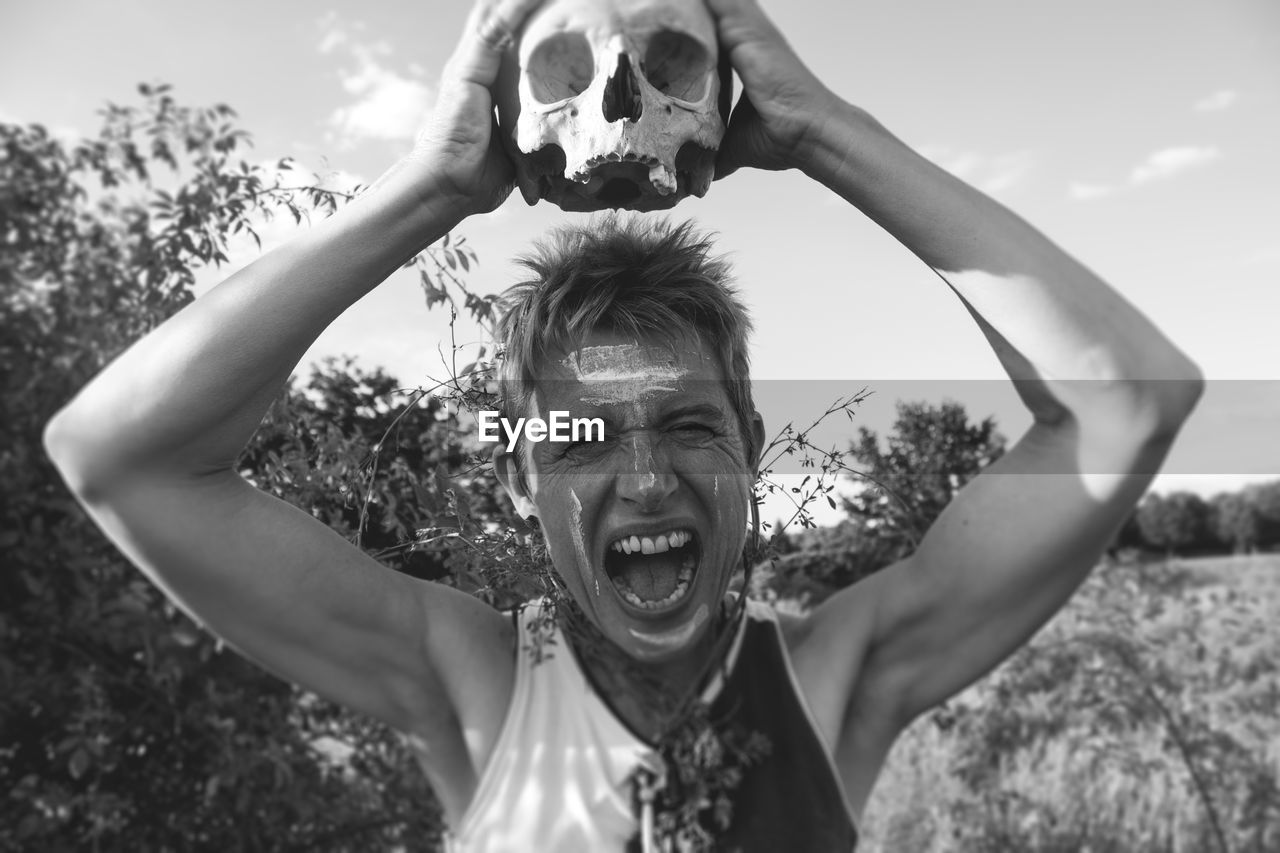 Mature Man Screaming While Holding Skull By Plants