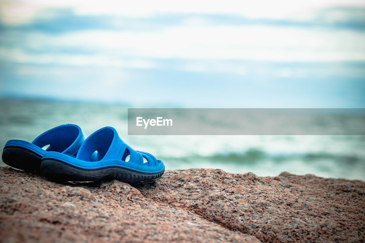 water, land, beach, shoe, sea, blue, nature, day, tranquility, sky, cloud - sky, selective focus, sand, beauty in nature, no people, slipper, scenics - nature, outdoors, tranquil scene, personal accessory
