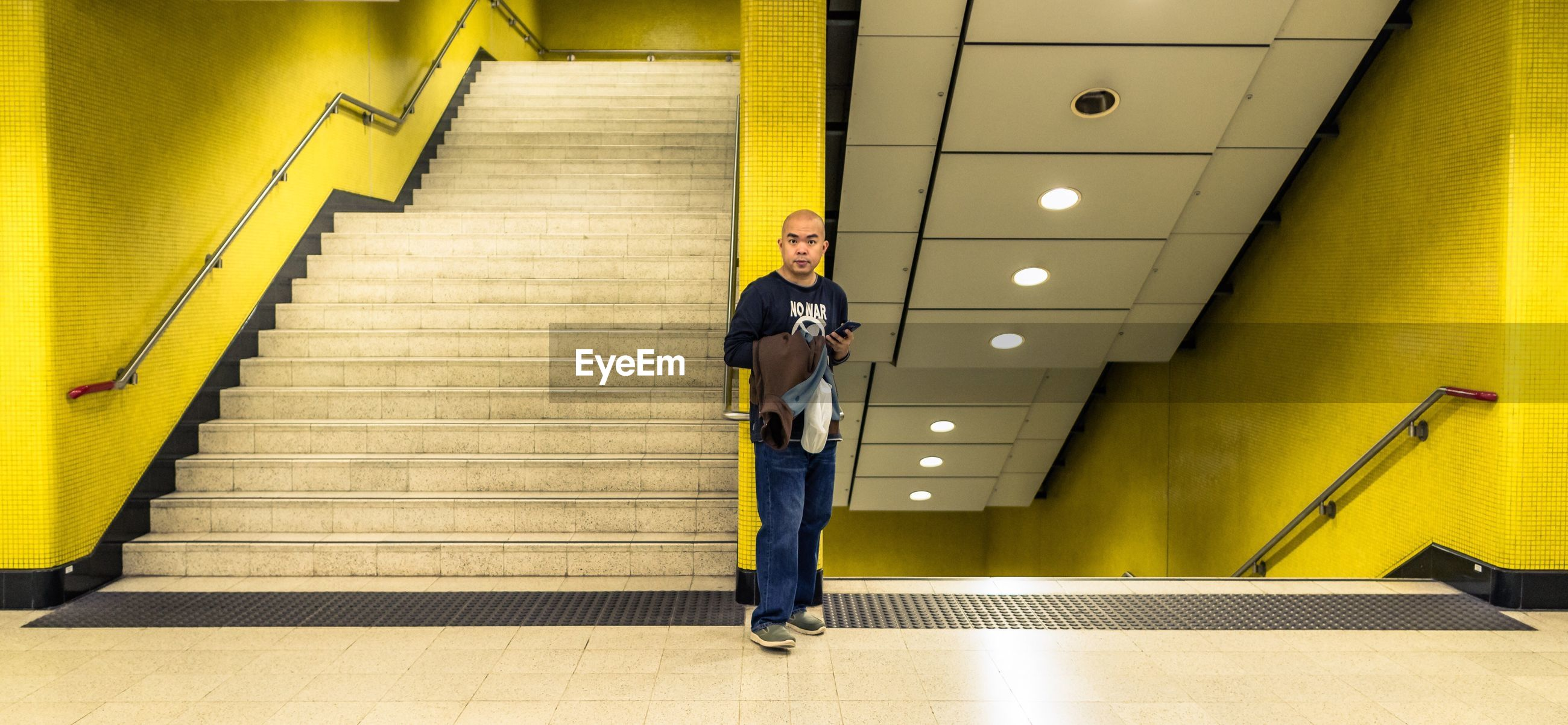 steps, indoors, steps and staircases, yellow, lifestyles, full length, staircase, escalator, men, wall - building feature, technology, walking, casual clothing, leisure activity, high angle view, convenience, the way forward, transportation