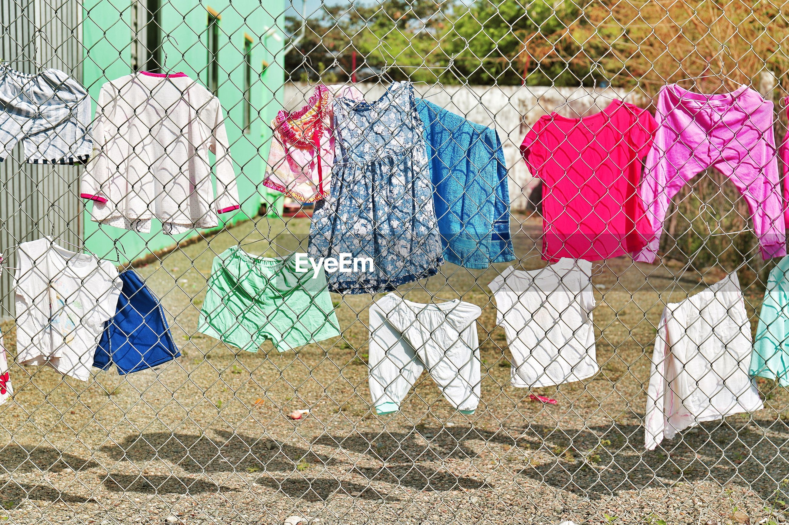 Clothes hanging on chainlink fence