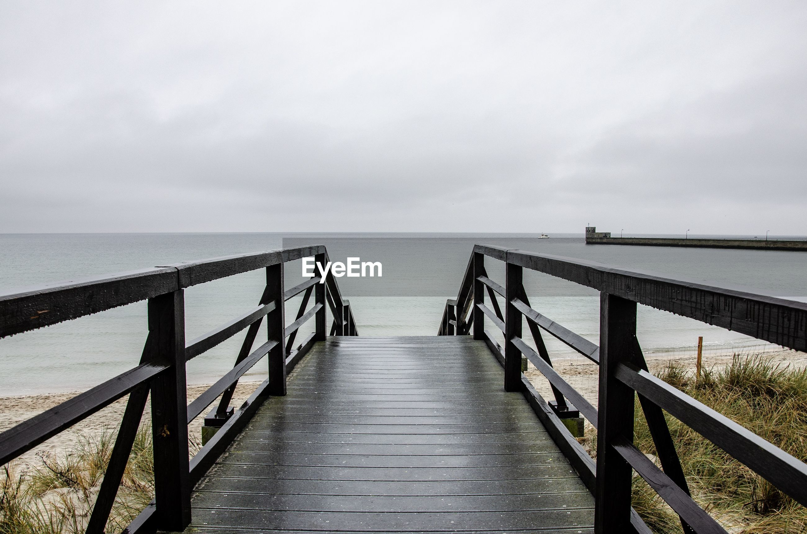 Empty wooden jetty leading to sea against sky