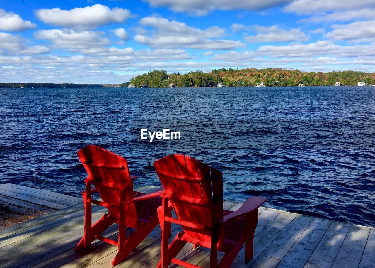 water, red, sea, chair, nature, sky, no people, tranquility, cloud - sky, beauty in nature, tranquil scene, outdoors, day, scenics, table, horizon over water