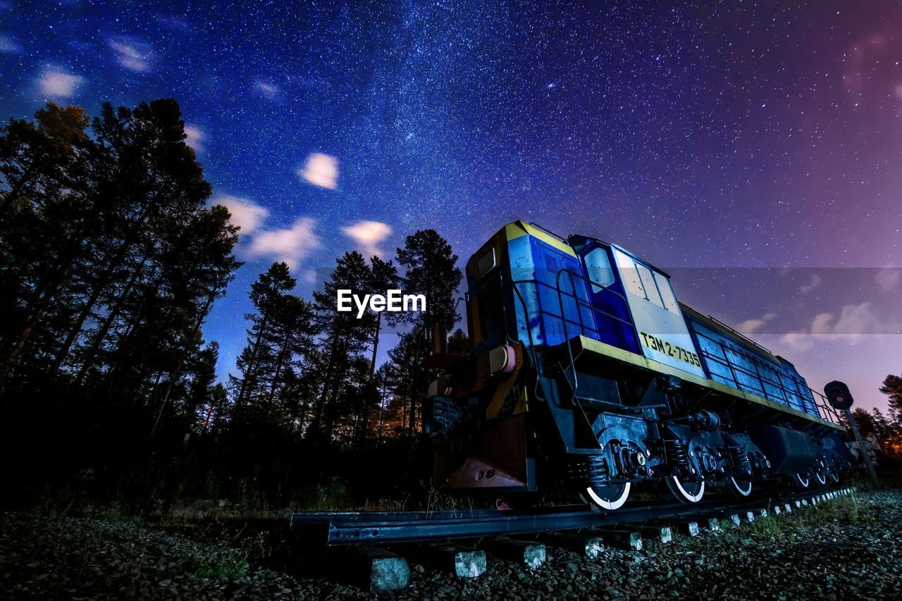 sky, night, nature, star - space, plant, rail transportation, tree, astronomy, low angle view, train, space, no people, train - vehicle, railroad track, transportation, track, star, outdoors, mode of transportation, star field