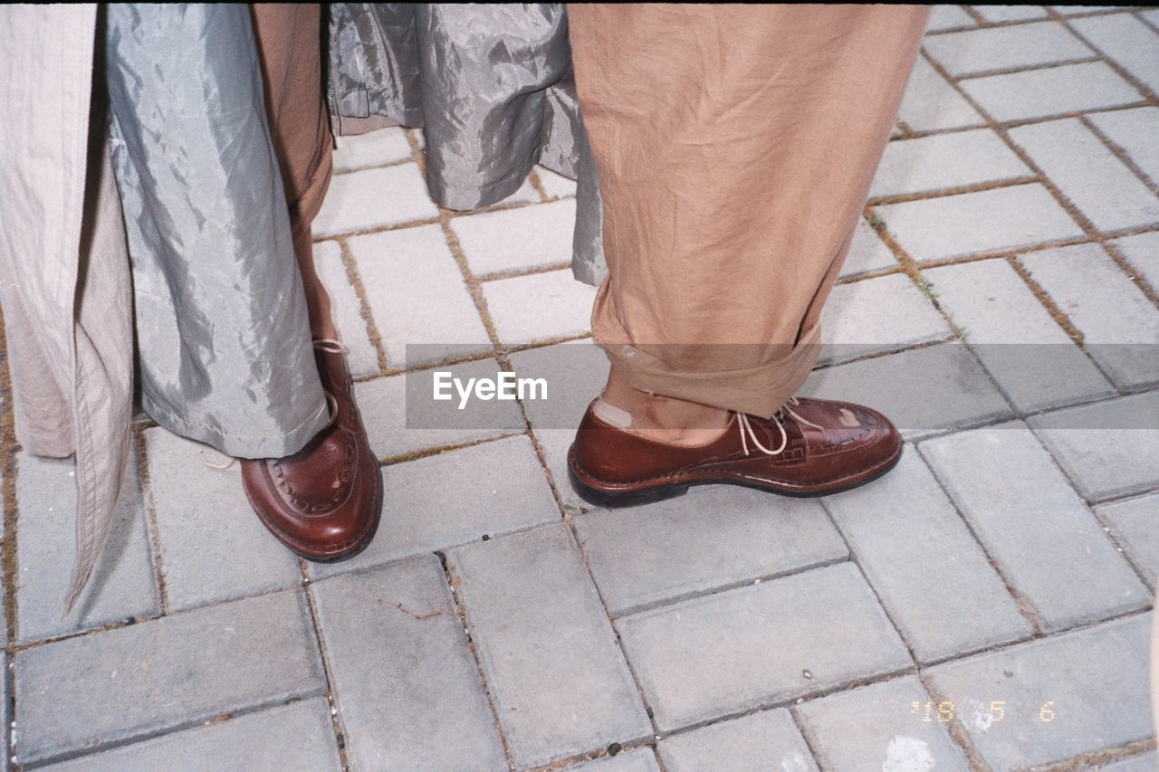 Low Section Of Man Wearing Shoes While Standing By Curtain On Paving Stone