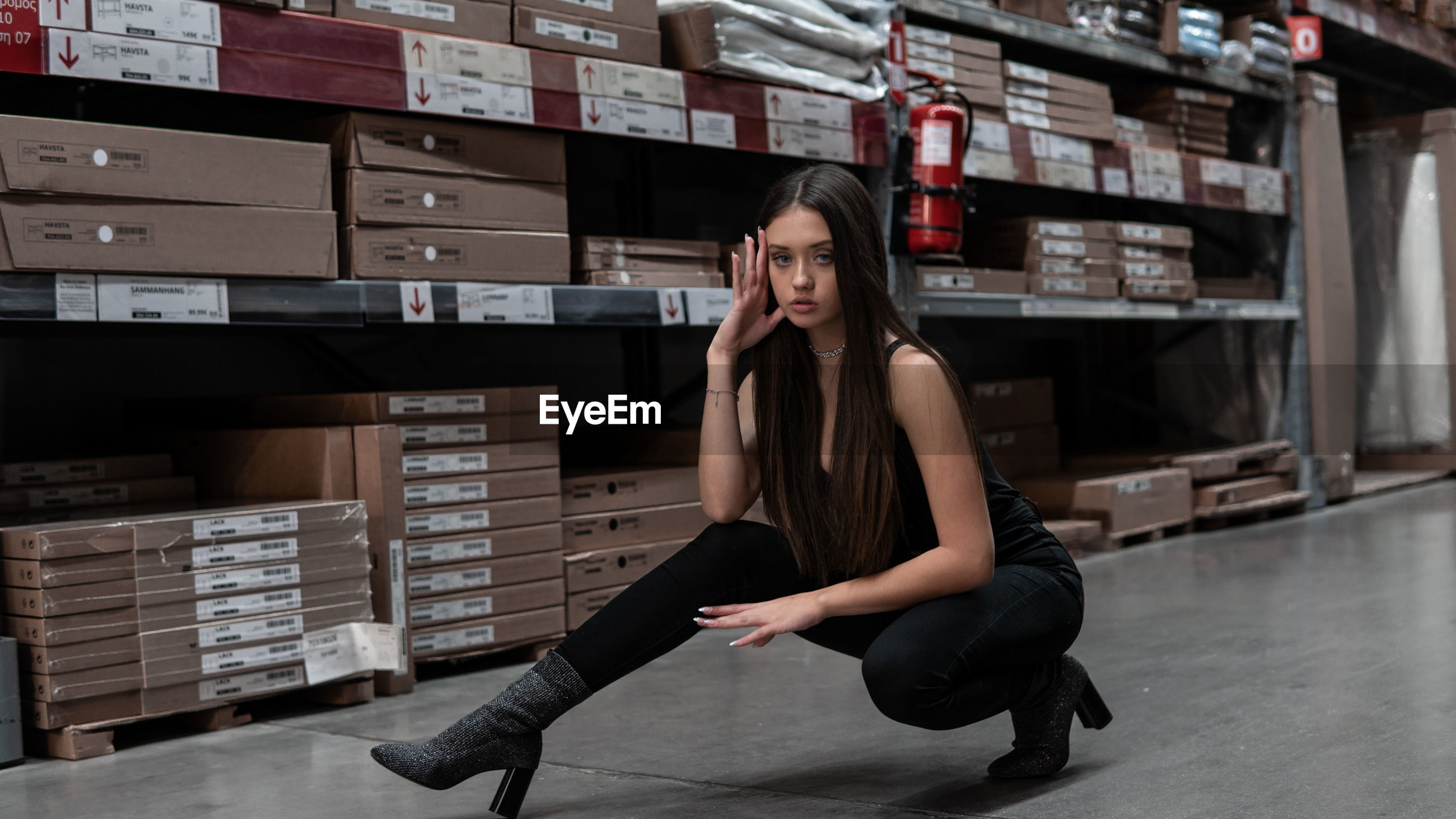 Full length portrait of young woman stretching on floor in warehouse