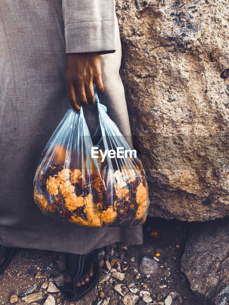 Low Section Of Man Holding Flowers In Plastic Bag