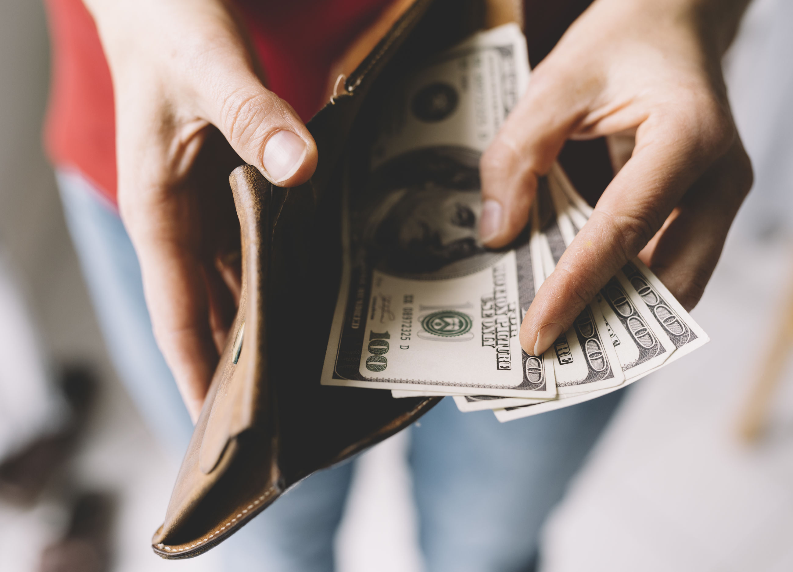 Midsection of man holding paper currency in wallet
