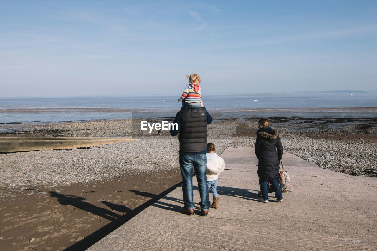 Family standing on shore against sky at beach