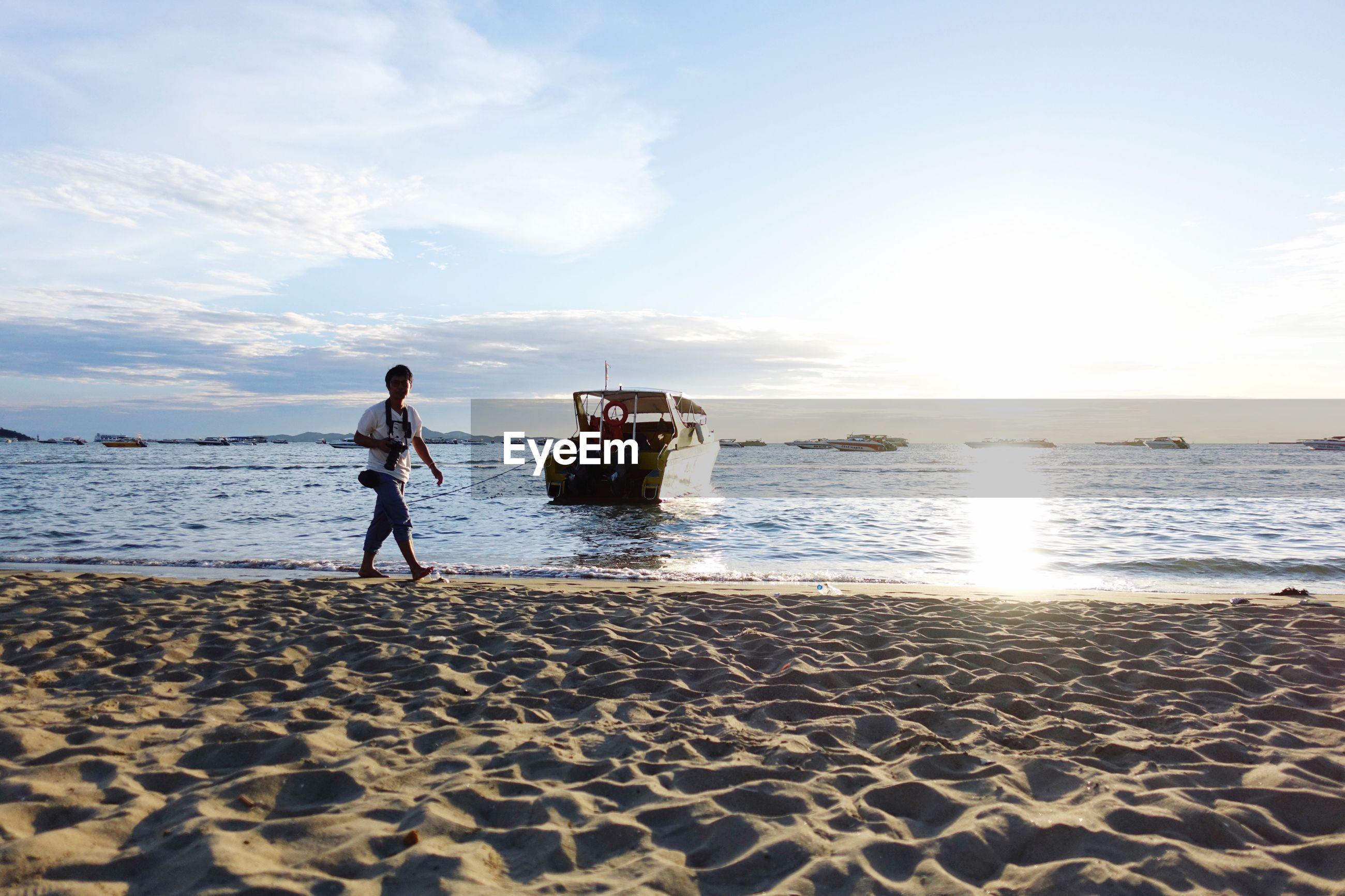 WOMAN STANDING ON BEACH AGAINST SEA AGAINST SKY