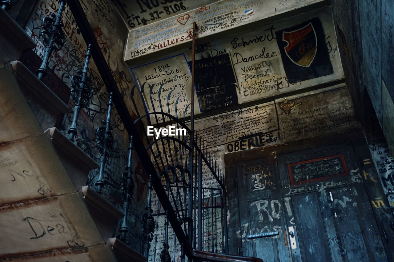 architecture, text, built structure, communication, no people, building, indoors, graffiti, wall - building feature, script, abandoned, damaged, sign, old, non-western script, weathered, day, low angle view, messy, deterioration, ruined