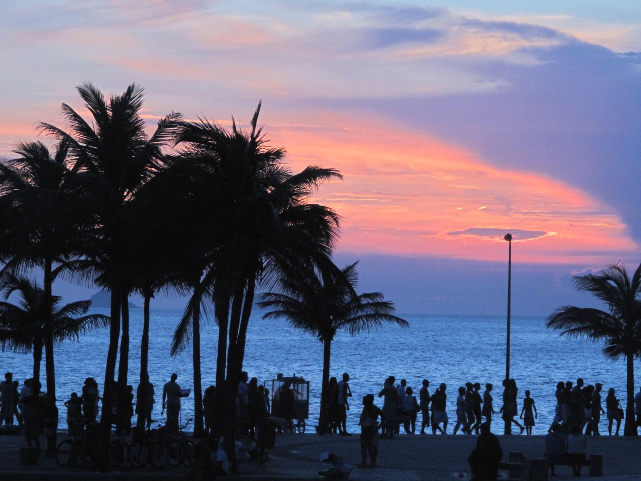 sky, sunset, tropical climate, palm tree, tree, sea, water, cloud - sky, silhouette, beach, beauty in nature, scenics - nature, nature, plant, group of people, horizon over water, land, orange color, tranquil scene, outdoors
