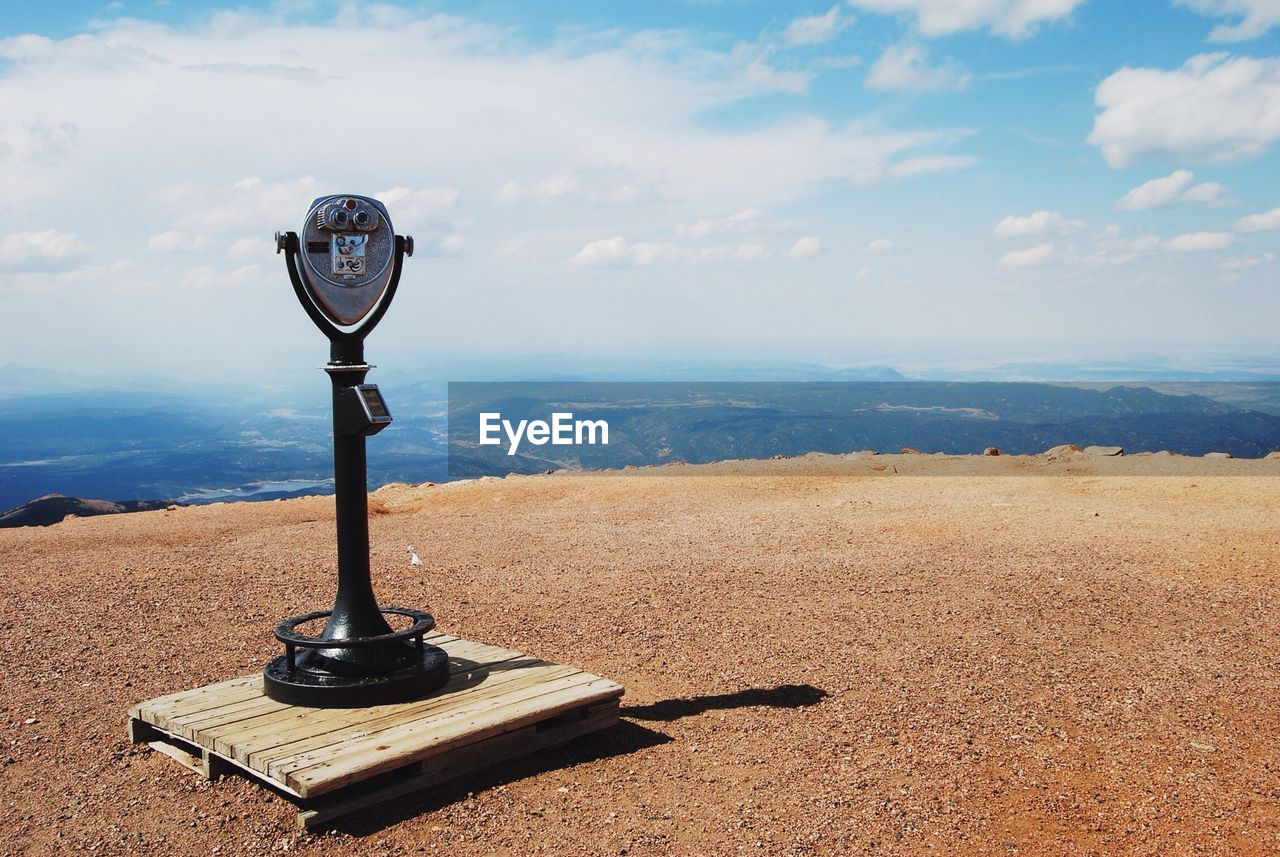 Coin-Operated Binoculars On Cliff Against Cloudy Sky
