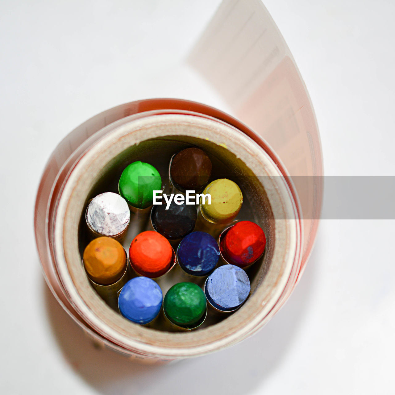 Directly above shot of colorful crayons in container on white background