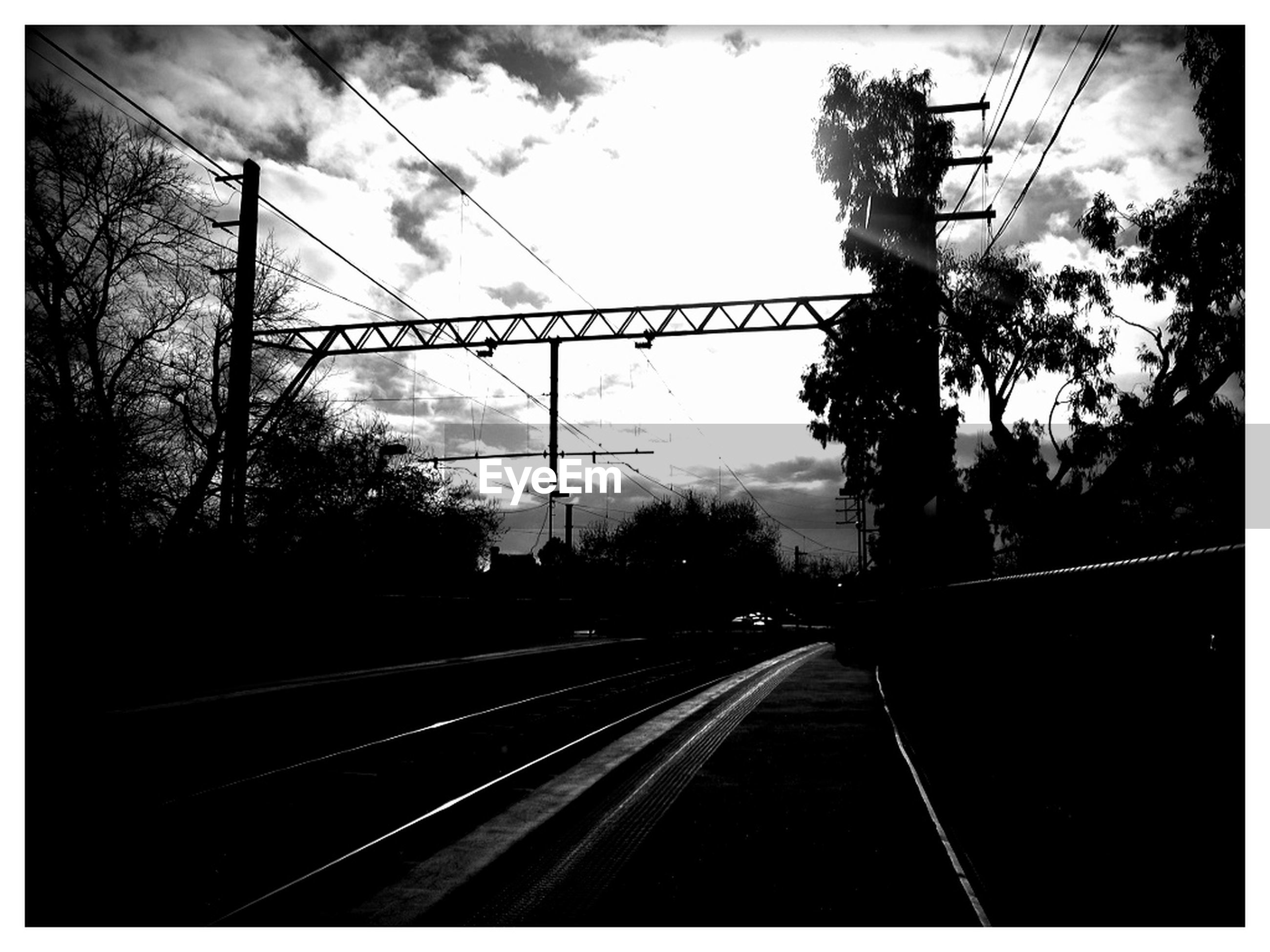 railroad track, transportation, transfer print, power line, sky, rail transportation, tree, electricity pylon, auto post production filter, the way forward, diminishing perspective, connection, power supply, silhouette, cable, electricity, vanishing point, public transportation, cloud - sky, power cable