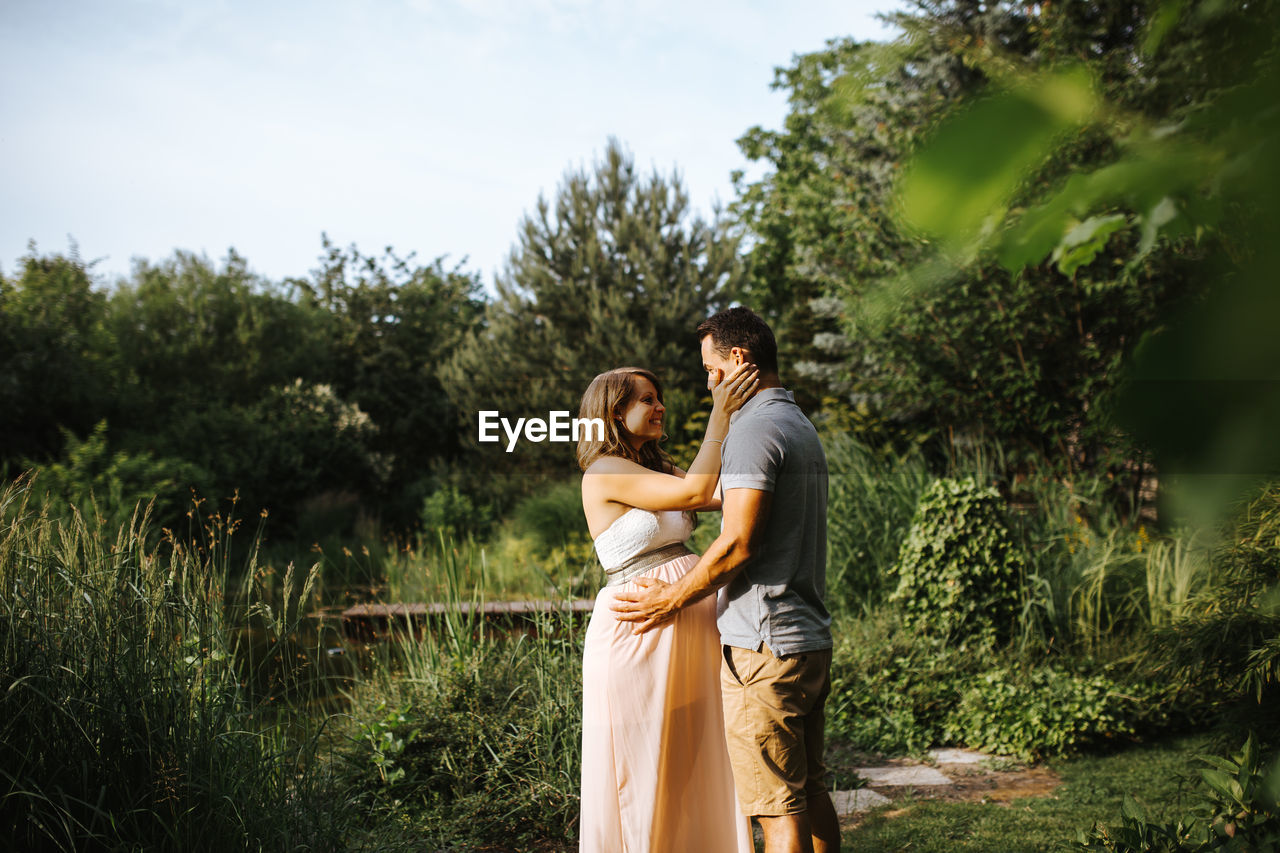 Side View Of Man Kissing Pregnant Wife While Standing Amidst Plants
