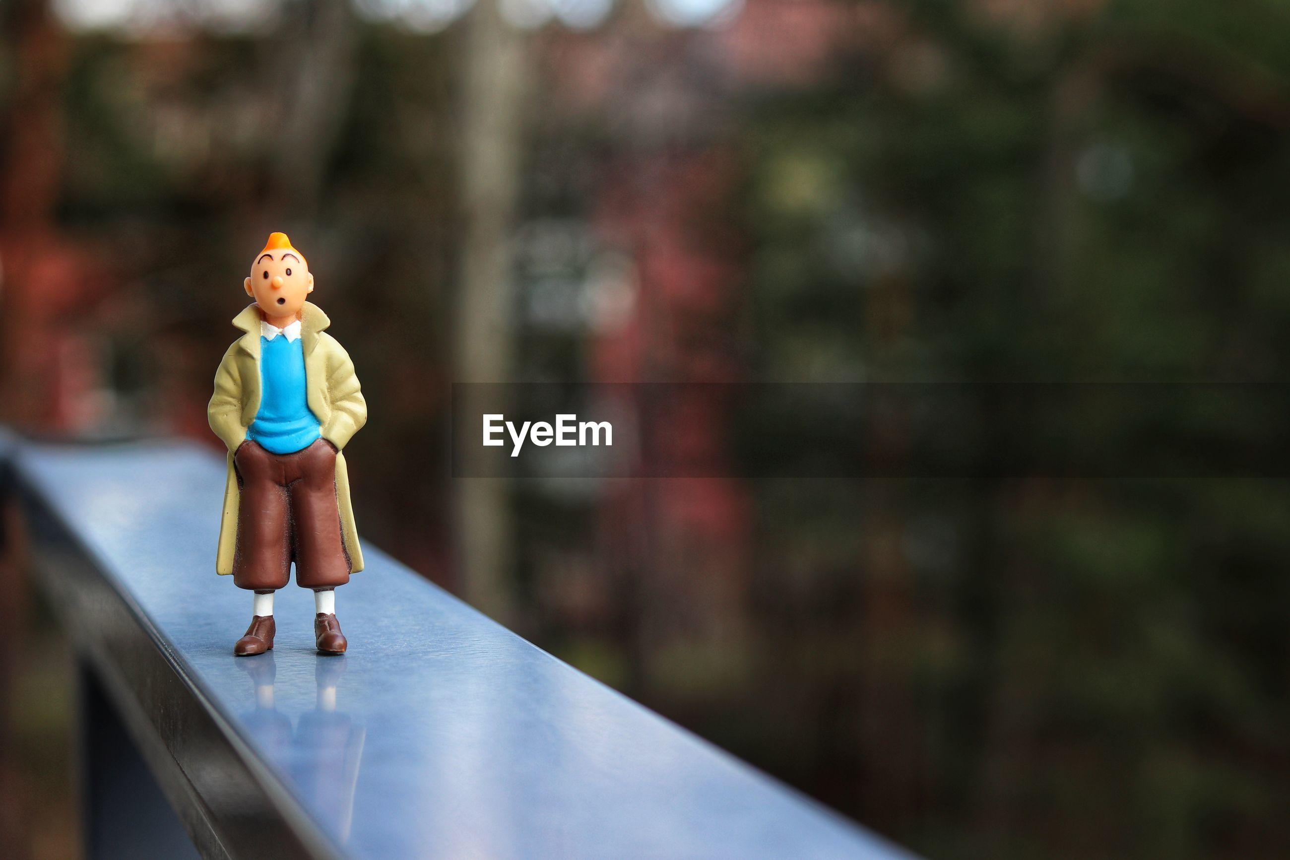 Close-up of figurine on railing