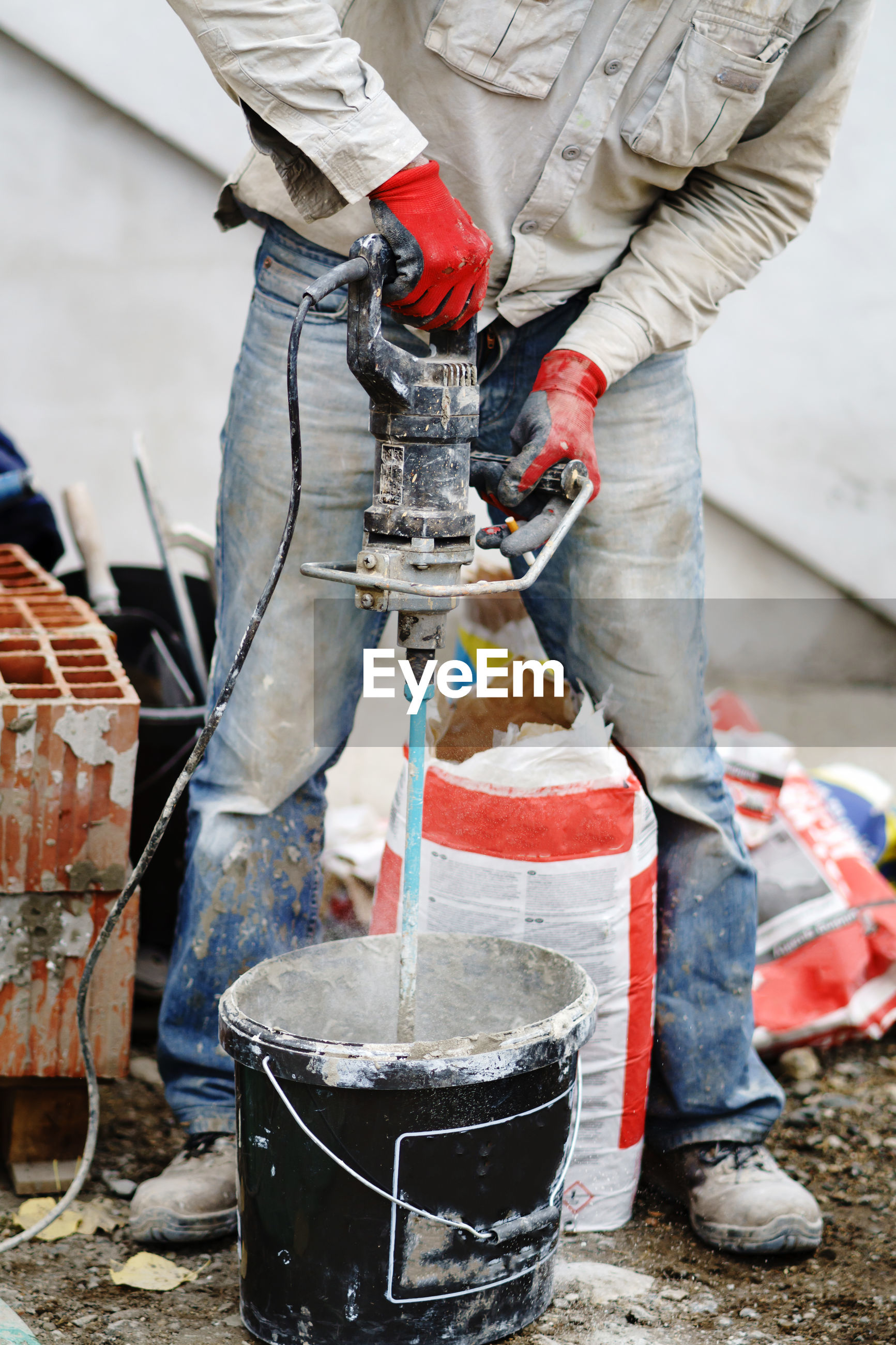 LOW SECTION OF MAN WORKING ON CONCRETE FLOOR