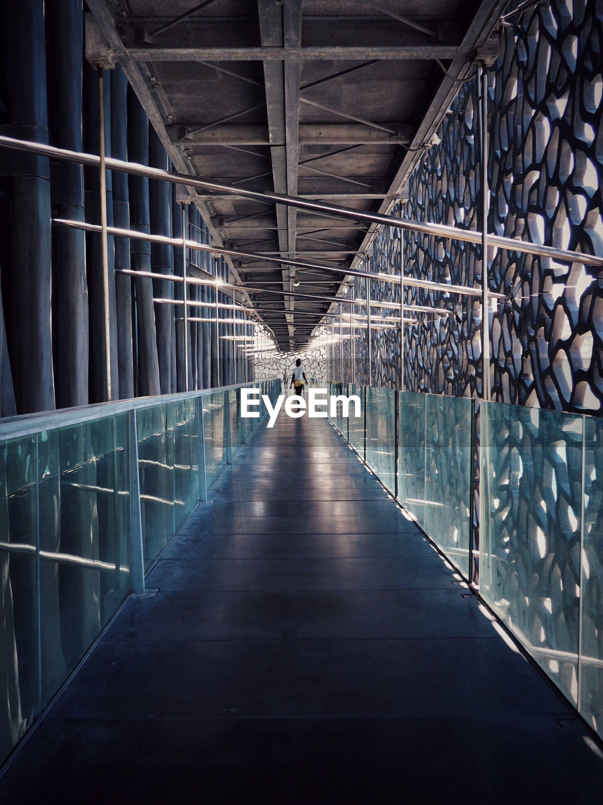 Rear view of person walking on walkway in museum