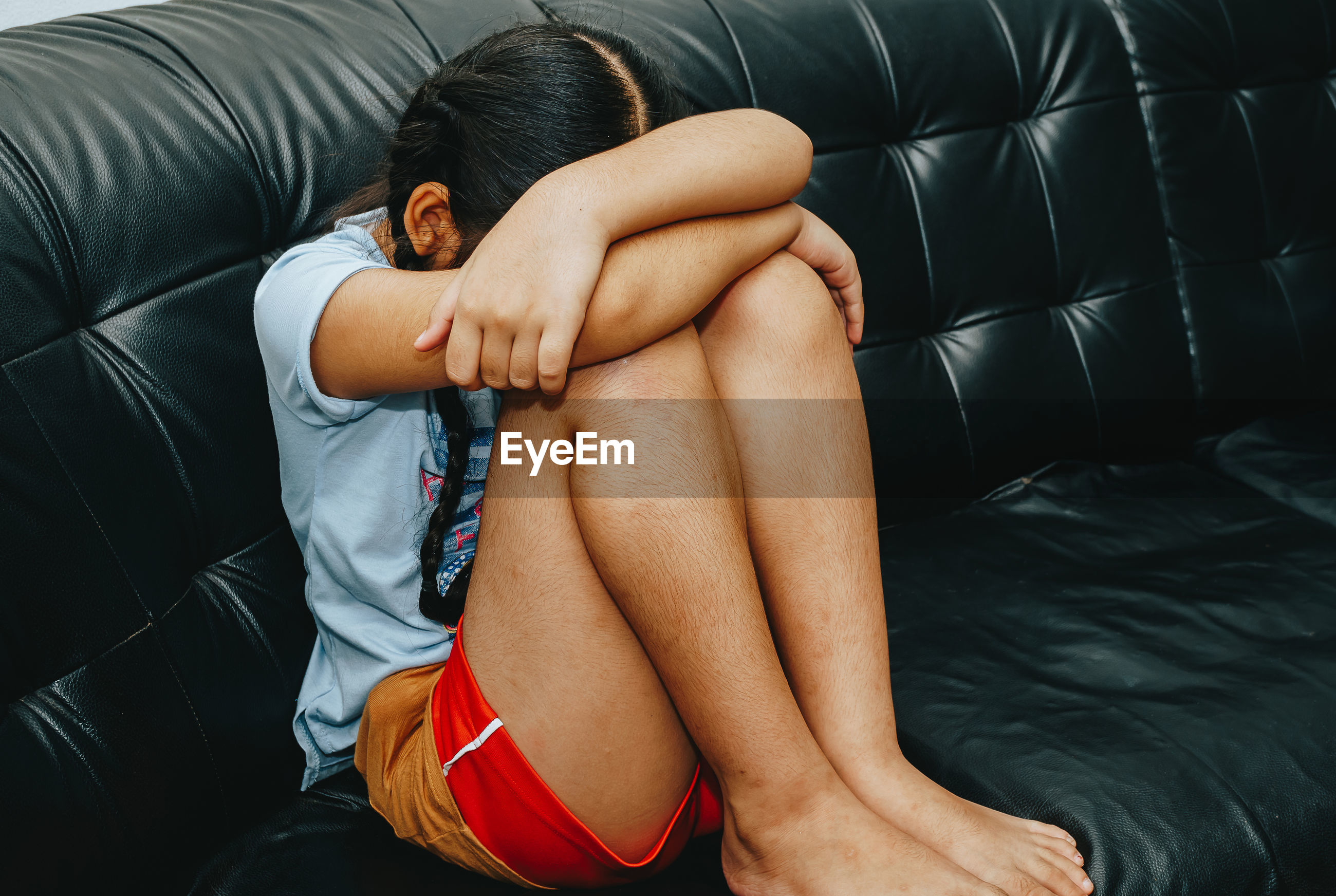Girl with head on knees sitting on sofa at home