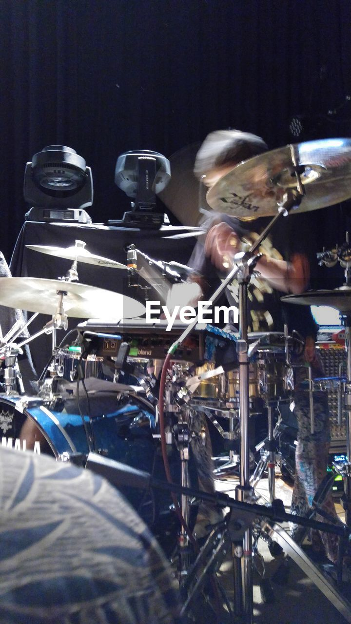 music, arts culture and entertainment, musical instrument, bicycle, drum kit, stage - performance space, indoors, men, recording studio, musician, real people, night, illuminated, drummer, close-up, jazz music, people