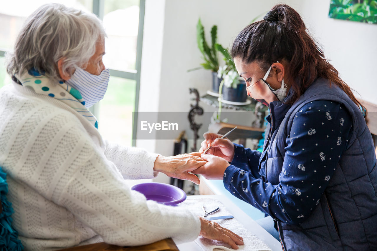 Woman wearing mask doing manicure of customer at home