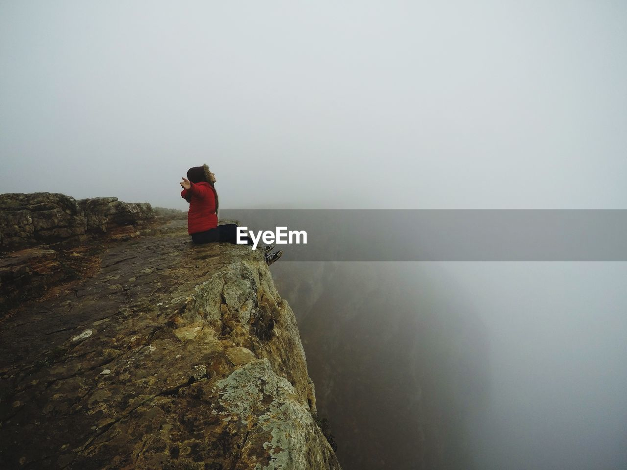 rock, rock - object, fog, solid, real people, sitting, leisure activity, lifestyles, one person, beauty in nature, nature, tranquility, adventure, mountain, sky, tranquil scene, scenics - nature, rock formation, vacations, outdoors, at the edge of, looking at view