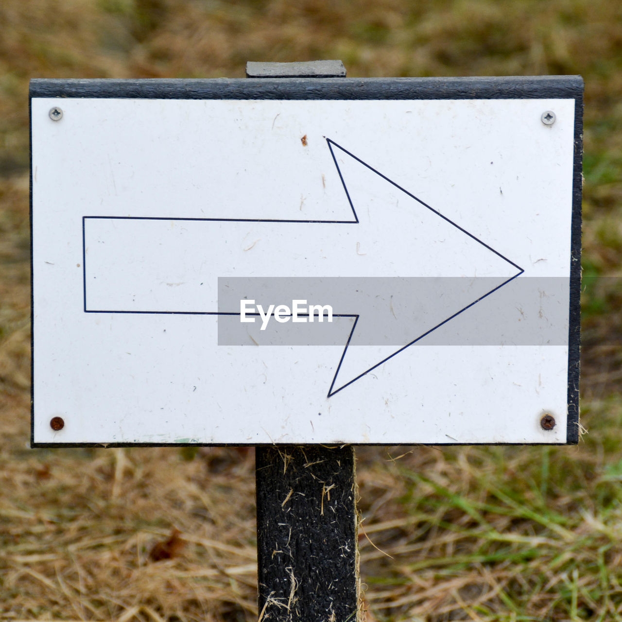 Close-up of arrow sign on field