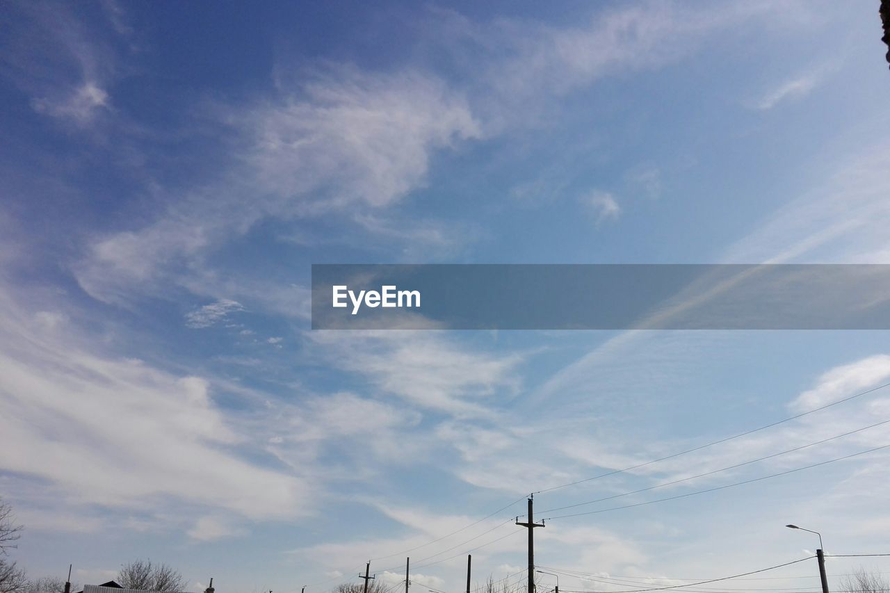 low angle view, cloud - sky, sky, no people, day, nature, blue, outdoors, scenics, beauty in nature, electricity pylon, technology, industrial windmill, vapor trail