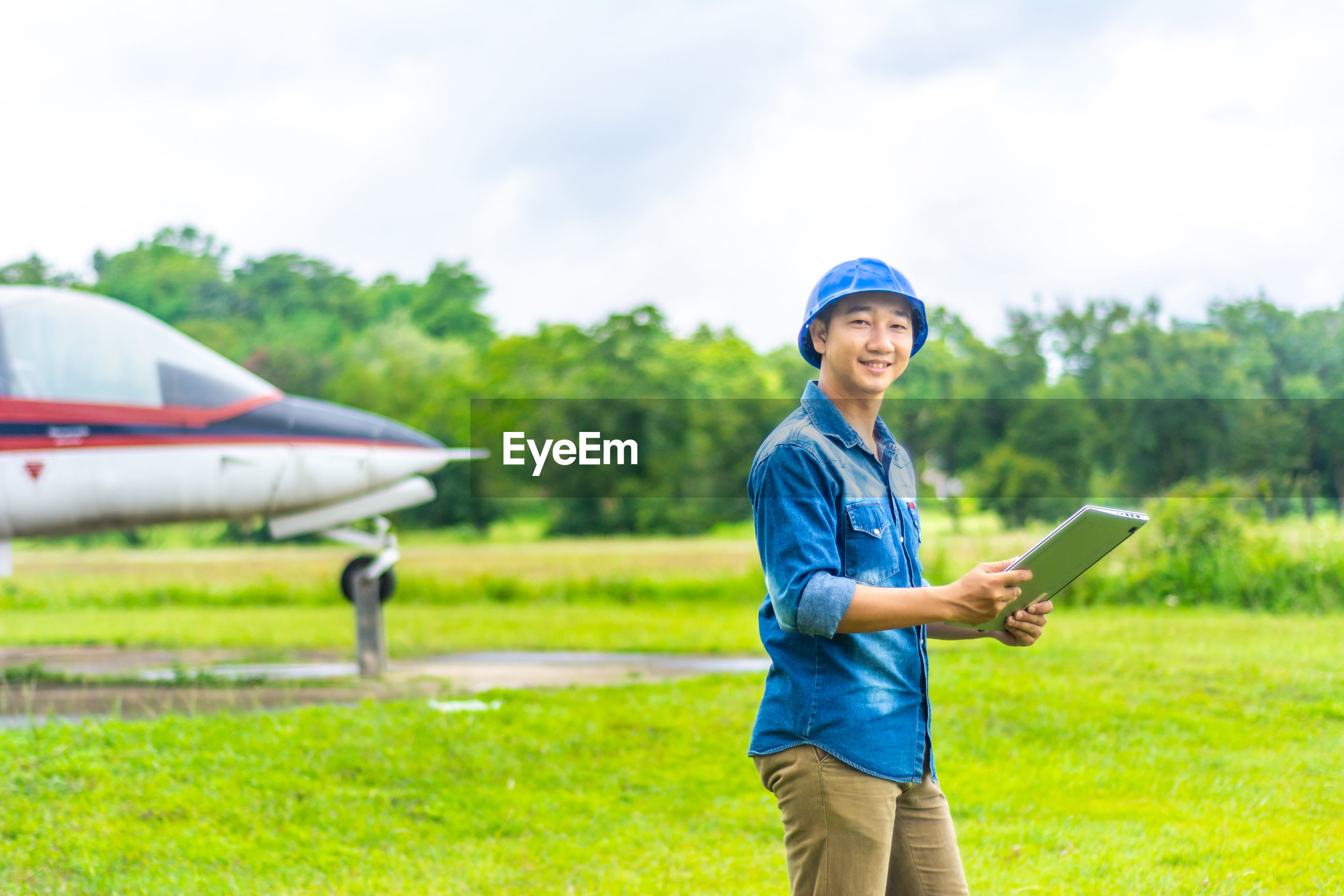 Portrait of smiling airplane mechanic standing against airplane on land