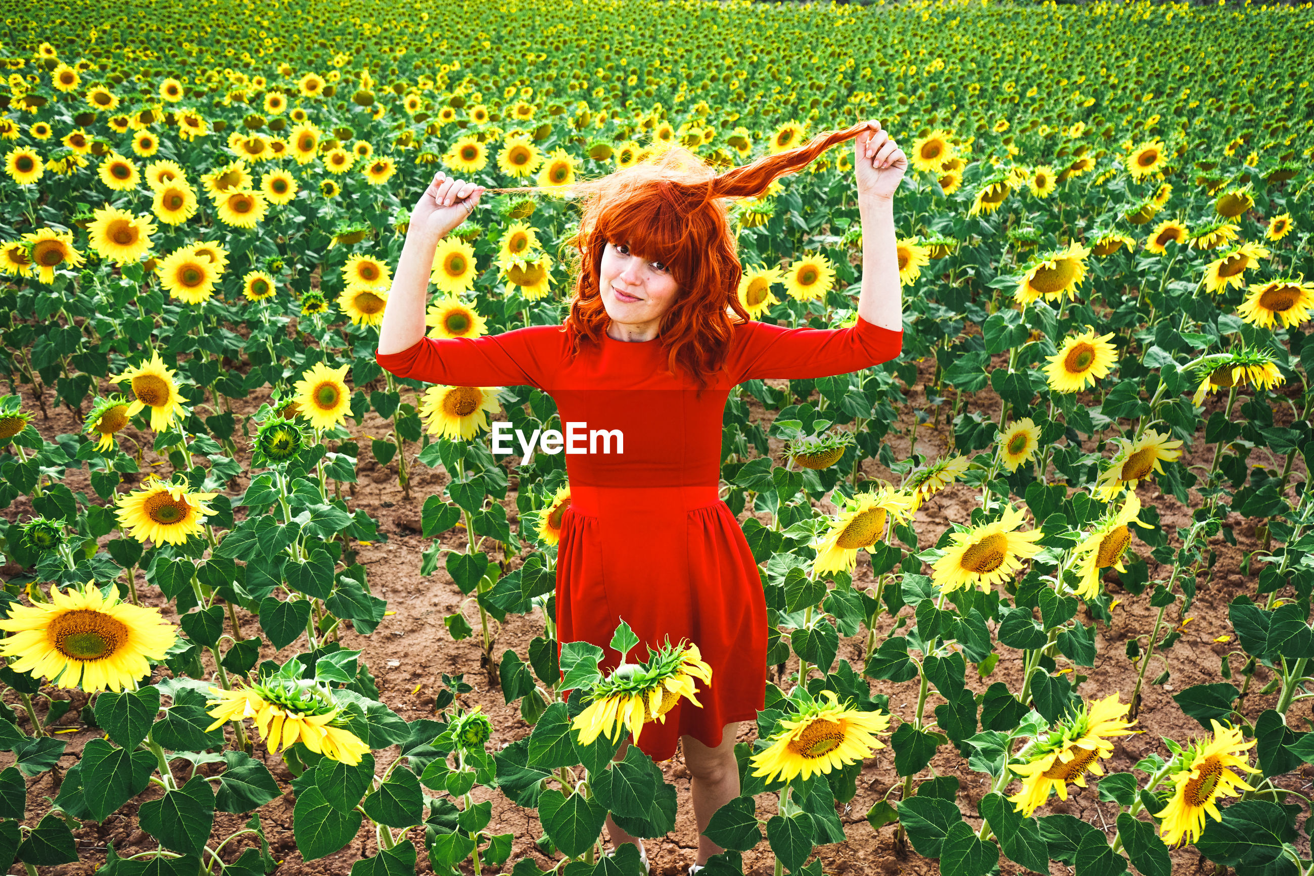 FULL LENGTH OF WOMAN STANDING BY YELLOW FLOWERS