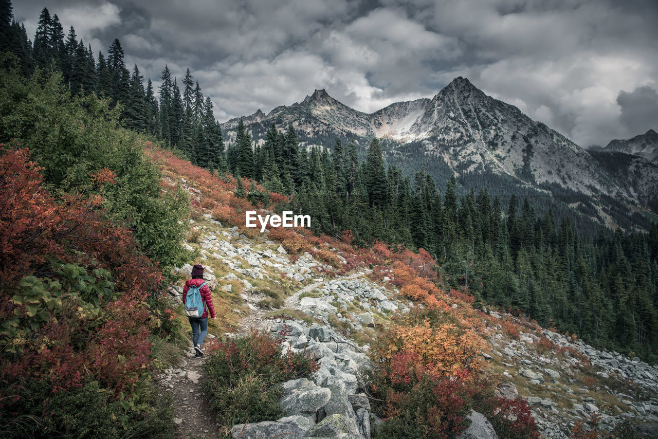 Rear view of woman hiking on mountain against cloudy sky